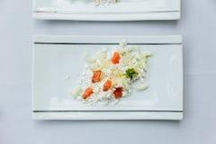 Modern Frans voorgerecht: verbrijzeling en besnoeiingskaas met gedobbelde die tomaat op witte rechthoekplaat wordt gediend stock afbeelding
