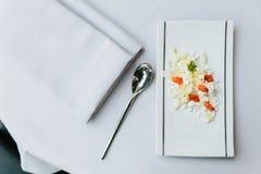 Modern Frans voorgerecht: verbrijzeling en besnoeiingskaas met gedobbelde tomaat diende op witte rechthoekplaat met zilveren lepe stock fotografie