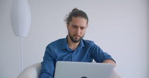 Modern freelancer med hästsvansarbeten med bärbara datorn som sitter i fåtölj i ljuskontoret som det är upptaget och koncentrerat stock video