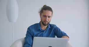 Modern freelancer with ponytail works with laptop sitting in armchair in light office being busy and concentrated. Modern freelancer with ponytail works with stock video