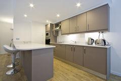 Modern fully fitted kitchen. With appliances and bar seating in white Stock Photography