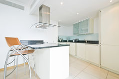 Modern fully fitted kitchen in vanilla white Royalty Free Stock Images
