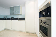 Modern fully fitted kitchen in vanilla white. With built in coffee machine and microwave with grill Stock Images