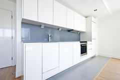 Modern fully fitted kitchen in white and gray Royalty Free Stock Photography