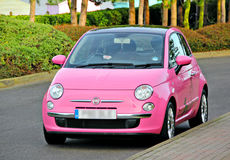 Modern fun pink small car. Photo of a modern funky pink car parked close to the sea and beach huts Stock Images