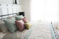 Bedroom with pastel pink and green accents pillows. Modern furniture in a cozy minimalist bedroom with pastel pink and green accents pillows Stock Photos