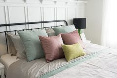 Bedroom with pastel pink and green accents pillows. Modern furniture in a cozy minimalist bedroom with pastel pink and green accents pillows Royalty Free Stock Photography