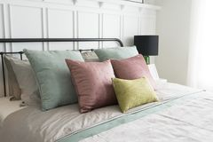 Bedroom with pastel pink and green accents pillows. Modern furniture in a cozy minimalist bedroom with pastel pink and green accents pillows Royalty Free Stock Images