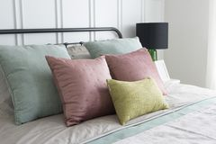 Bedroom with pastel pink and green accents pillows. Modern furniture in a cozy minimalist bedroom with pastel pink and green accents pillows Stock Images