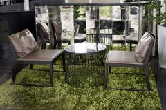 Modern furniture having brown leather chair and marble table. On green grass carpet at the coffee shop Stock Photo