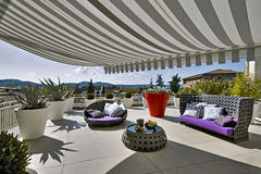 Modern furniture on the terrace. Sofa and armchairs on the modern terrace with awnings and planter box Stock Images