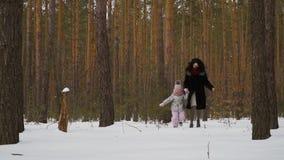 Modern går i vinterskog med den gulliga lilla dottern arkivfilmer