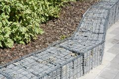 Modern Gabion fence with stones in wire mesh. Gabion wire mesh fencing with natural stones. Landscape design Royalty Free Stock Photos