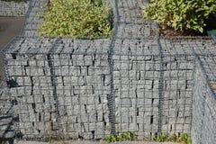 Modern gabionstaketv?gg med stenar i tr?dingrepp i tr?dg?rddesignen F?ktning f?r Gabion tr?dingrepp med naturliga stenar royaltyfria foton
