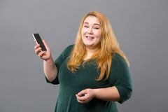 Joyful obese woman holding her phone. Modern gadget. Joyful obese woman holding her phone while making a call Royalty Free Stock Photography