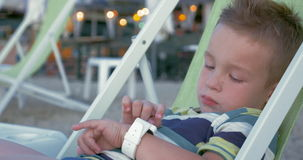 Modern gadgets for any age. Little boy in chaise-longue at the seaside using smart watch. Modern gadgets for modern generation stock video