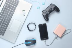 Modern gadgets and devices on a gray background. Laptop,power bank, earphones, smart bracelet, gamepad, headphones, USB flash drive, PC mouse. Flat lay royalty free stock photo