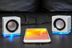 Small white speakers connected to a smartphone stock images