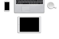 Modern gadgets lying on white surface. Laptop computer, tablet and smart phone and white empty cup on white background. Top view o Royalty Free Stock Image