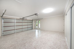 Modern Garage Interior. The inside of a modern 2 bay home garage with pebble floor and dual auto garage door Stock Photography