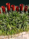 Modern garden: red ceramic sculptures grass border Royalty Free Stock Photography