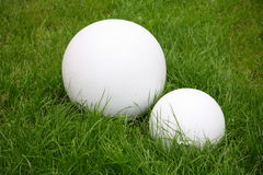 Modern garden sculpture - two white ball on green grass lawn. Royalty Free Stock Photo