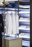 Modern garderob i lägenheten med kläder och hyllor för skor Skjortor och klänningar, hattar och skor i en trendig dressing Royaltyfri Foto