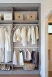 Modern garderob med rad av den vita klänningen och skor som hänger i wardr Royaltyfria Bilder
