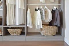 Modern garderob med rad av den vita klänningen och skor som hänger i wardr Arkivbilder
