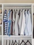 Modern garderob med rad av skjortor som hänger i garderob Arkivbild