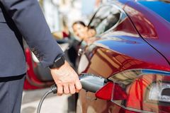 Close up of a fuel nozzle being put into the car. Modern gas station. Close up of a fuel nozzle being put into the car by a confident smart nice businessman Stock Images