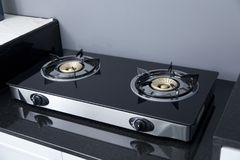 Modern gas stove on counter top in modern home kitchen. Close up of brand new, modern gas stove on counter top in contemporary modern home kitchen royalty free stock photography