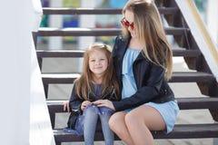 Modern gekleidete Mutter und Tochter auf der Straße im Frühjahr Lizenzfreies Stockfoto