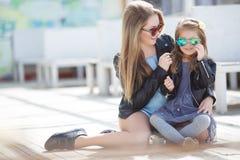 Modern gekleidete Mutter und Tochter auf der Straße im Frühjahr Stockbilder