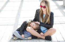Modern gekleidete Mutter und Tochter auf der Straße im Frühjahr Stockfotos