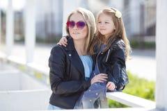 Modern gekleidete Mutter und Tochter auf der Straße im Frühjahr Stockbild