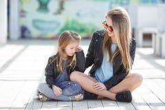 Modern gekleidete Mutter und Tochter auf der Straße im Frühjahr Lizenzfreie Stockfotos