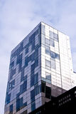 Modern generic residential building. A modern glass and steel generic residential  building on a cloudy sky Stock Photography