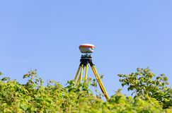 A modern geodesic receiver operates autonomously in the field among wild raspberry thickets royalty free stock images
