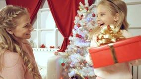 Modern ger en gåva för nytt år till hennes dotter arkivbilder