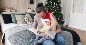 Modern ger en gåva till ett barn för jul arkivfilmer