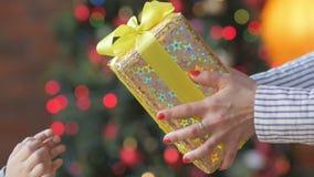 Modern ger en gåva till hennes barn mot bakgrunden av ljusa festliga ljus stock video