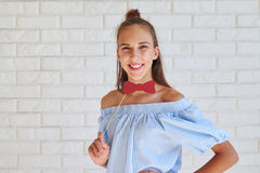 Modern girl in casual clothes holding paper bow-tie and smiling Royalty Free Stock Photography