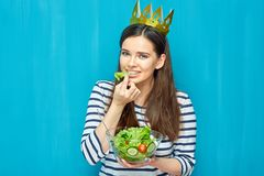 Modern girl eating green salad from glass bowl. Queen of healthy food on blue wall background Royalty Free Stock Photography