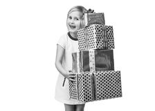 Happy trendy child on white holding pile of Christmas gifts. Modern Girl. happy trendy child in white dress isolated on white background holding pile of Royalty Free Stock Image
