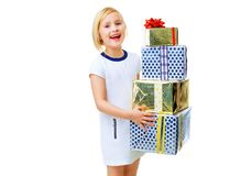 Happy trendy child on white holding pile of Christmas gifts. Modern Girl. happy trendy child in white dress isolated on white holding pile of Christmas present Royalty Free Stock Photo