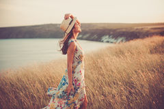 Modern girl in light summer dress. Side portrait of Modern girl in light summer dress with stylish hat enjoying sunset Stock Photography