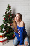Modern girl near New Year's tree Royalty Free Stock Image