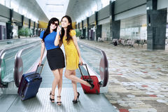 Modern girls standing in airport hall Royalty Free Stock Photo