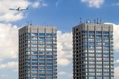 Modern glas en concrete wolkenkrabbers en een vliegtuig in de hemel Stock Foto's